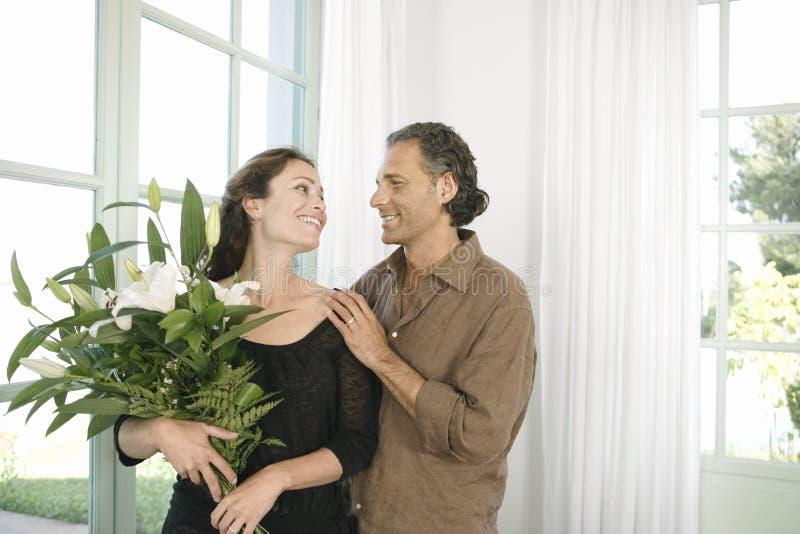 Homem que dá flores à mulher. imagem de stock