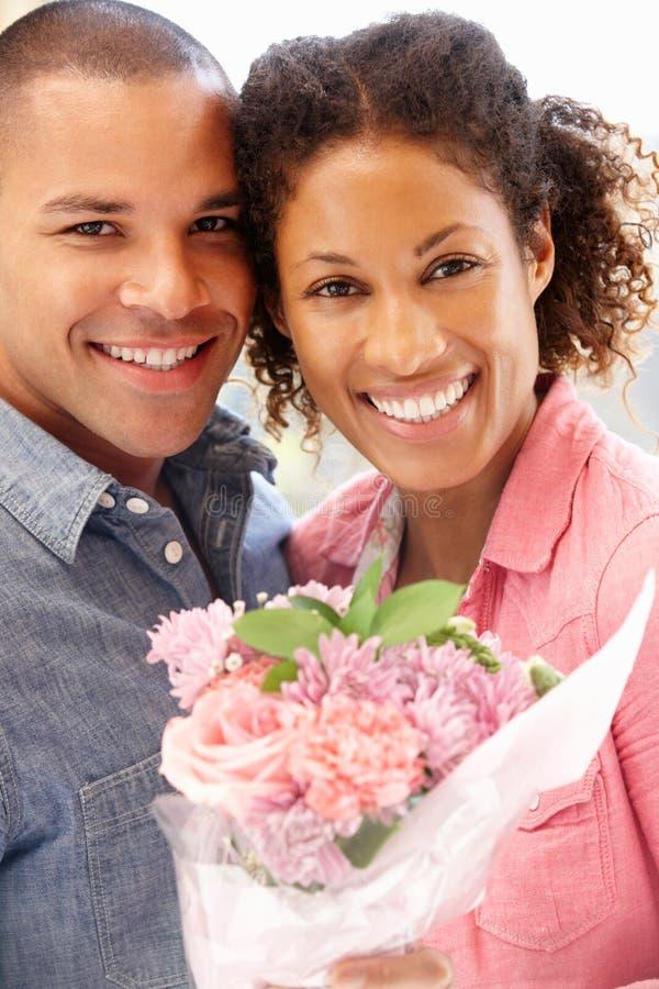 homem que dá flores à mulher imagem de stock royalty free