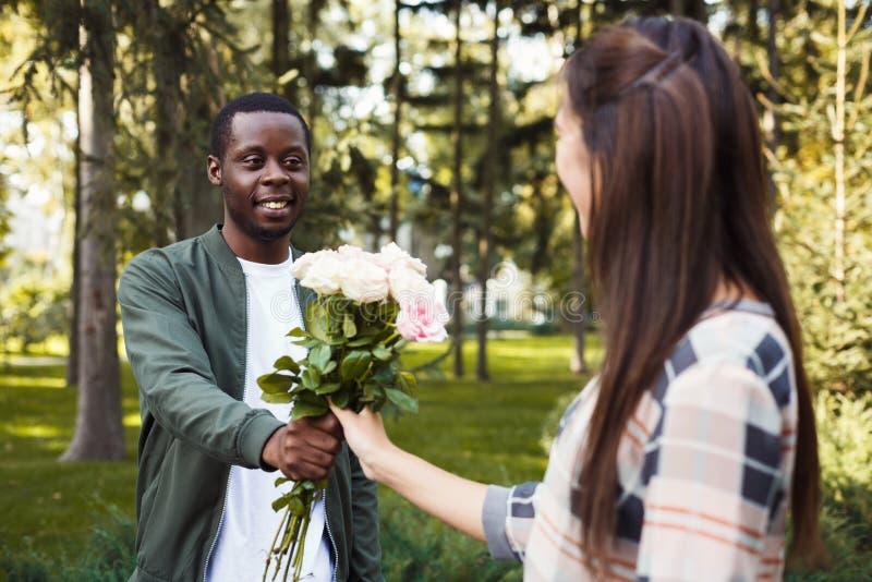 Homem que dá flores para sua amiga bonita fotografia de stock