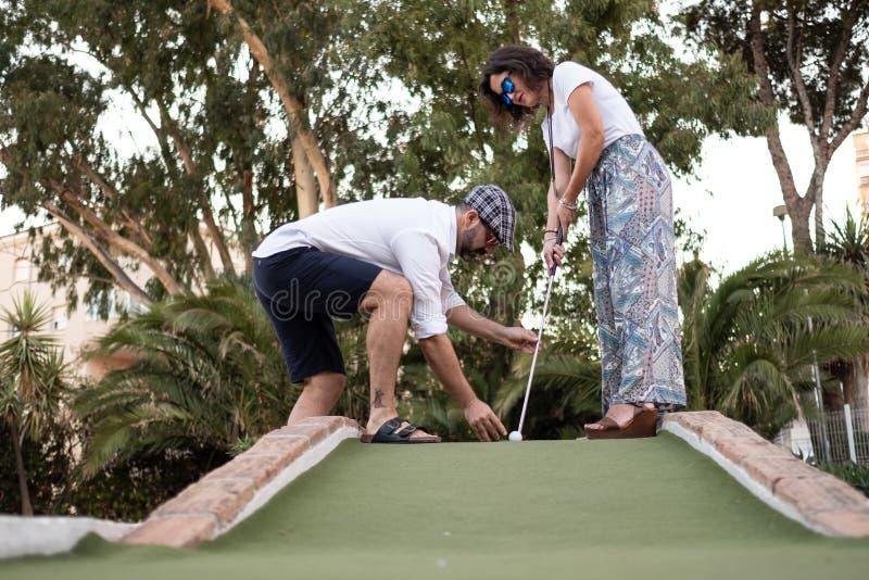 Homem que dá a lição de golfe a uma mulher foto de stock