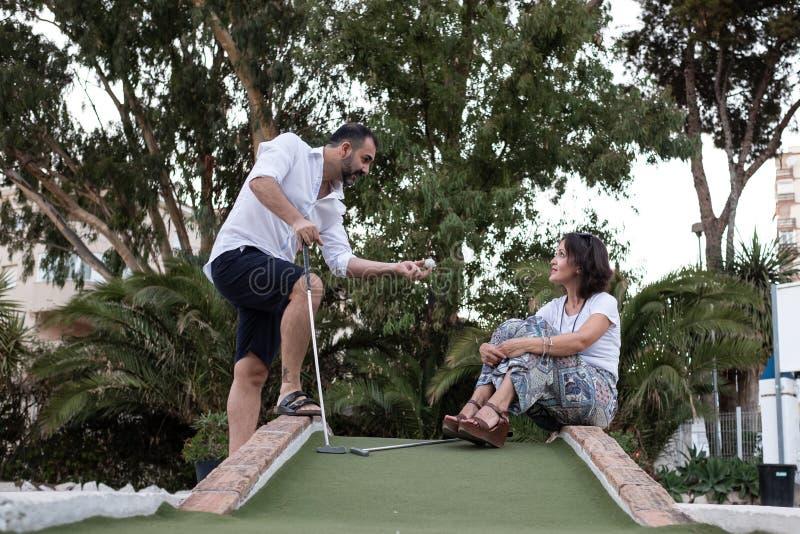 Homem que dá a lição de golfe a uma mulher fotos de stock