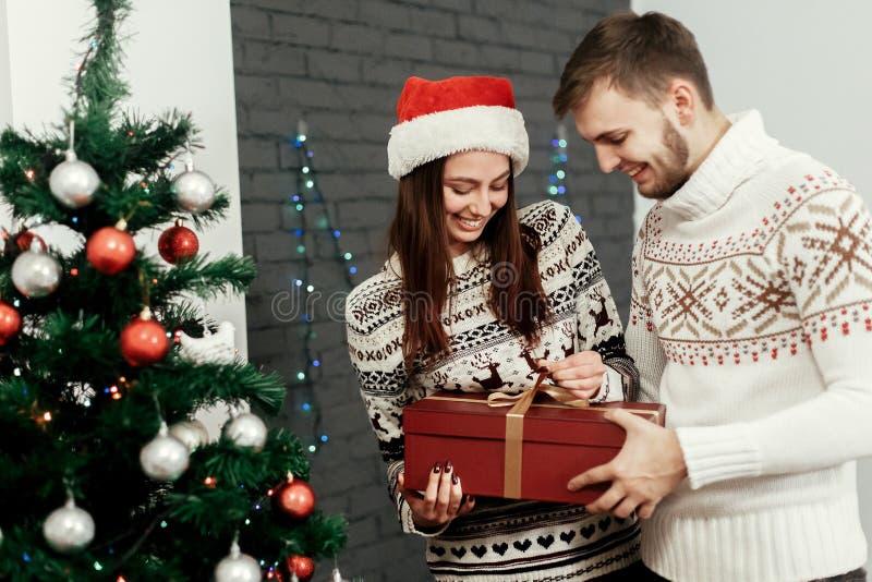 Homem que dá o presente grande a sua mulher smilin à moda feliz da família imagens de stock