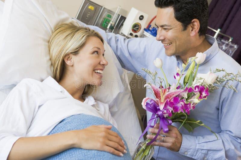 Homem que dá a sua esposa grávida flores imagem de stock royalty free