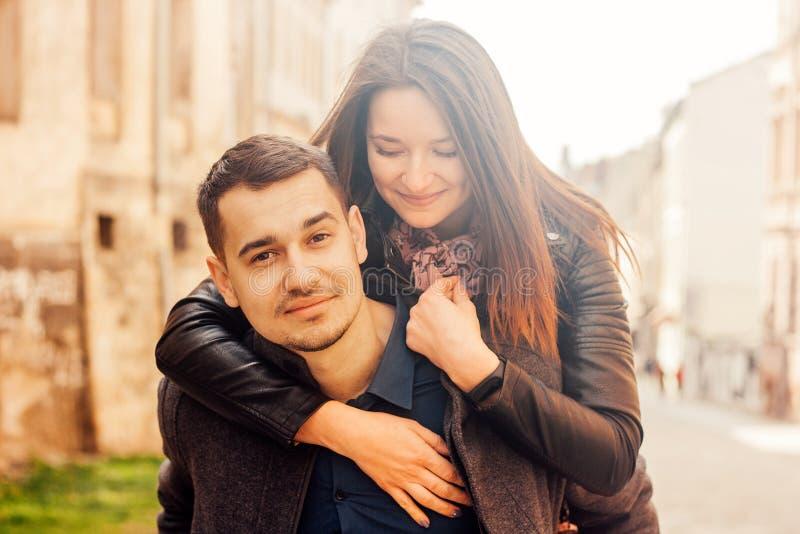 Homem que d? ?s cavalitas o passeio a sua amiga Pares felizes na rua foto de stock royalty free