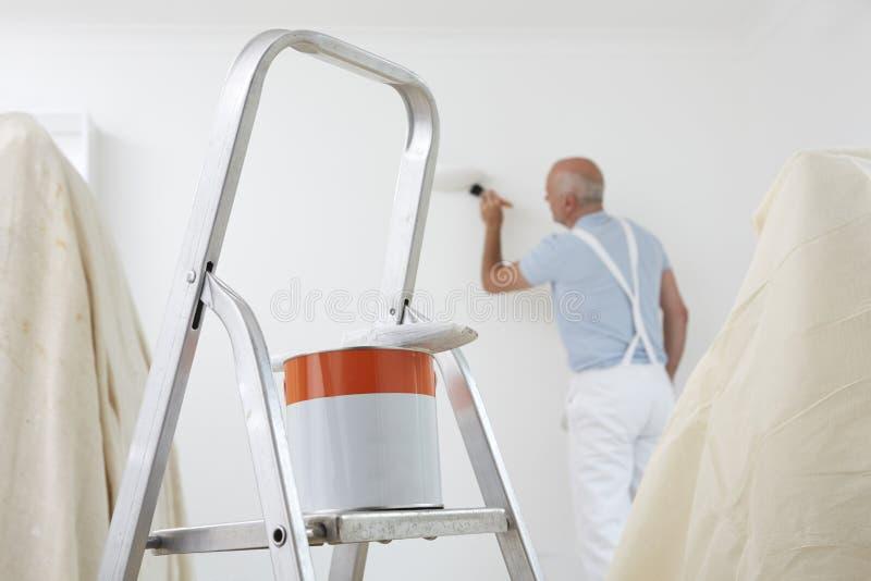 Homem que decora a sala com a lata da pintura e da escova no primeiro plano fotografia de stock royalty free