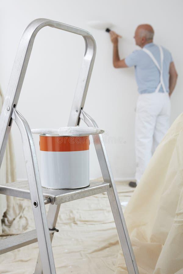 Homem que decora a sala com a lata da pintura e da escova no primeiro plano imagens de stock royalty free