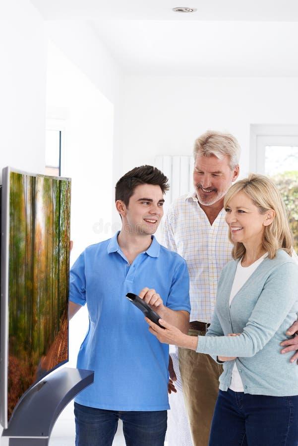 Homem que demonstra a televisão nova aos pares maduros em casa imagem de stock
