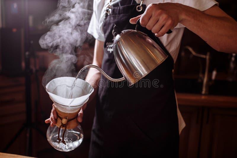 Homem que derrama a água quente para fazer o café fotografia de stock royalty free
