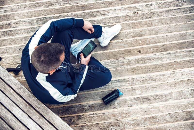 Homem que descansa após o exercício do corredor ou da aptidão e que usa o telefone celular e a água potável ou a proteína imagem de stock royalty free