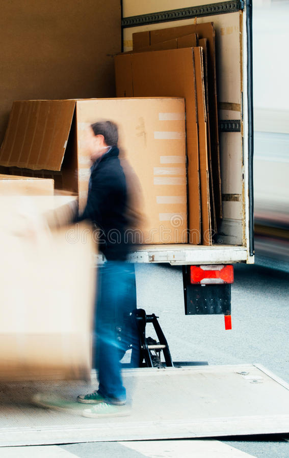 Homem que descarrega caixas de um caminhão foto de stock