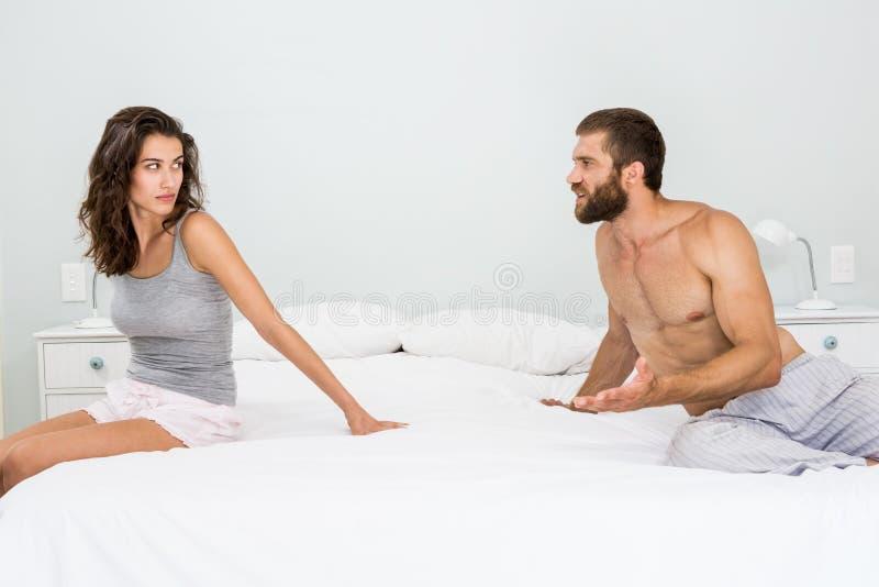 Homem que discute com a mulher na cama imagens de stock royalty free