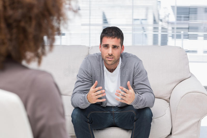 Homem que diz a terapeuta seus problemas fotografia de stock