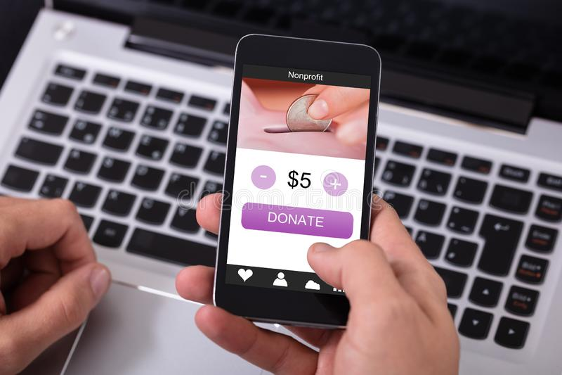 Homem que doa o dinheiro no telefone celular imagem de stock