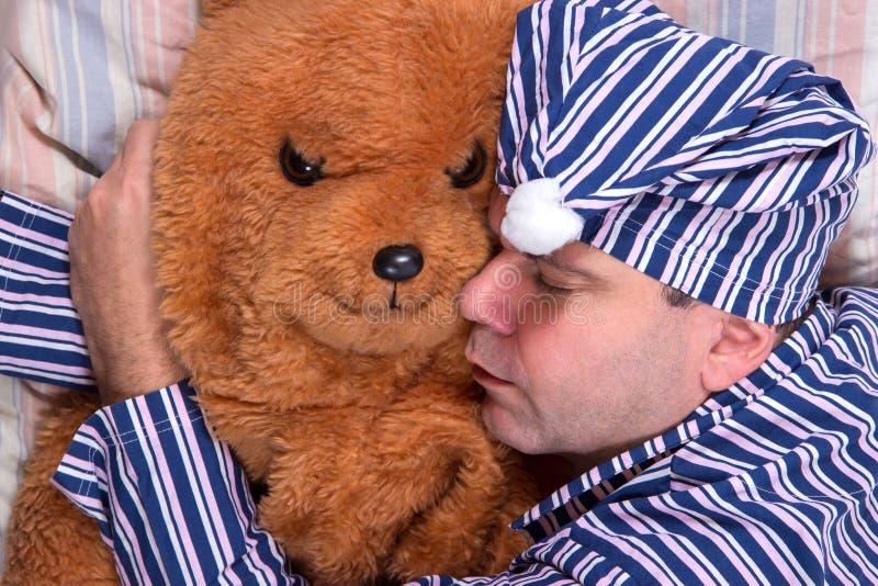 Homem que dorme com um urso de peluche imagem de stock royalty free
