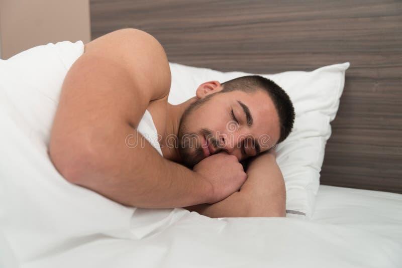 Homem que dorme confortavelmente em sua cama imagens de stock