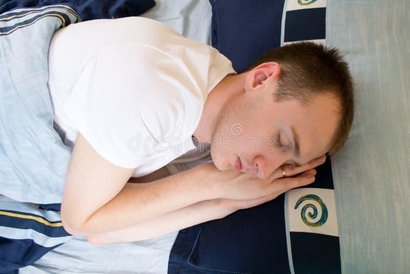 Homem que dorme confortavelmente na cama imagem de stock royalty free