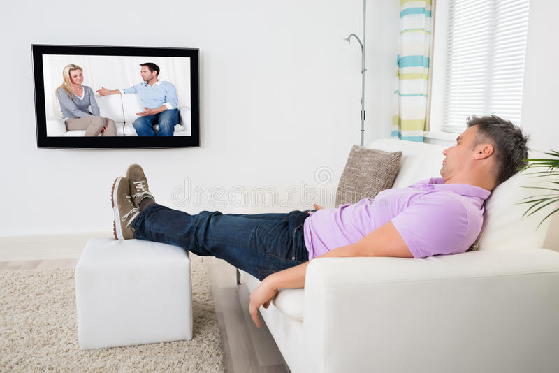 Homem que dorme em Sofa While Watching Television imagens de stock