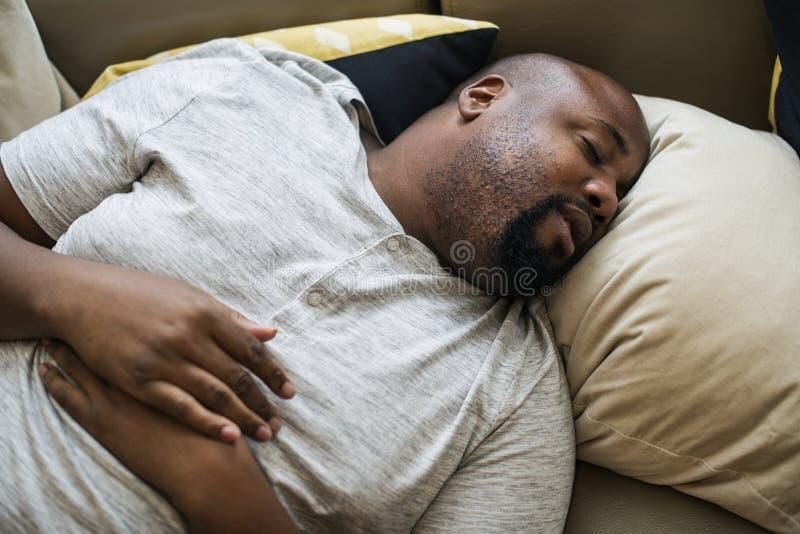 Homem que dorme em sua cama fotografia de stock royalty free