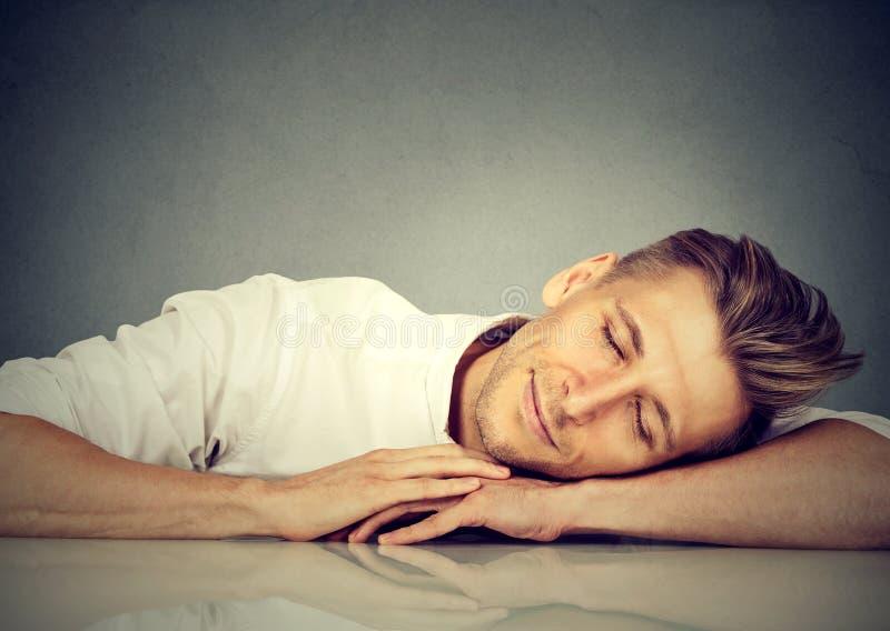 Homem que dorme em uma mesa imagem de stock royalty free