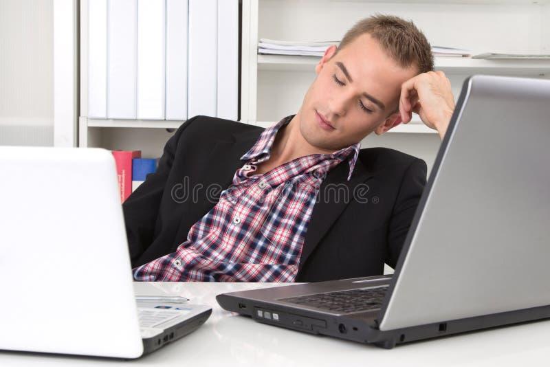 Homem que dorme no local de trabalho imagens de stock