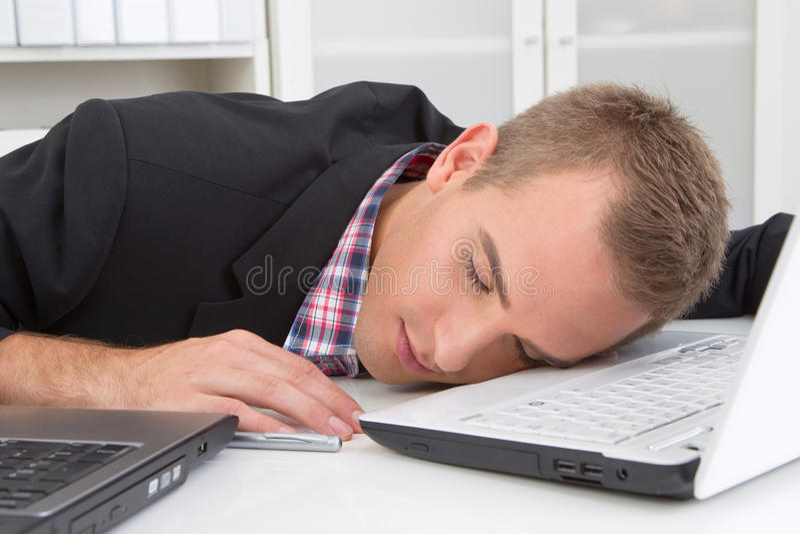 Homem que dorme no local de trabalho imagens de stock royalty free