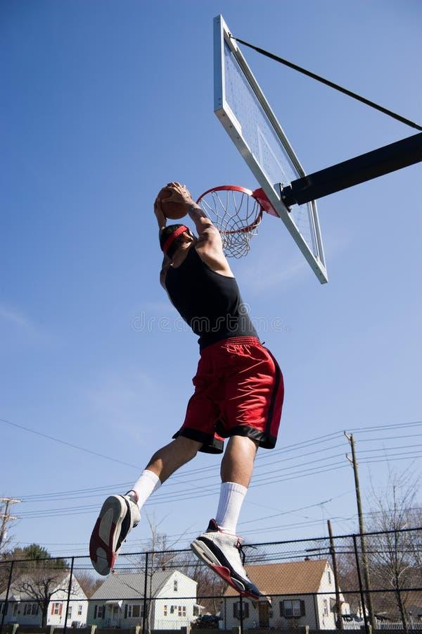 Homem que Dunking o basquetebol fotografia de stock