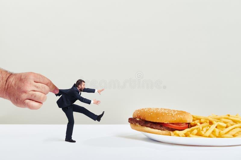 Homem que eagering para uma comida lixo foto de stock