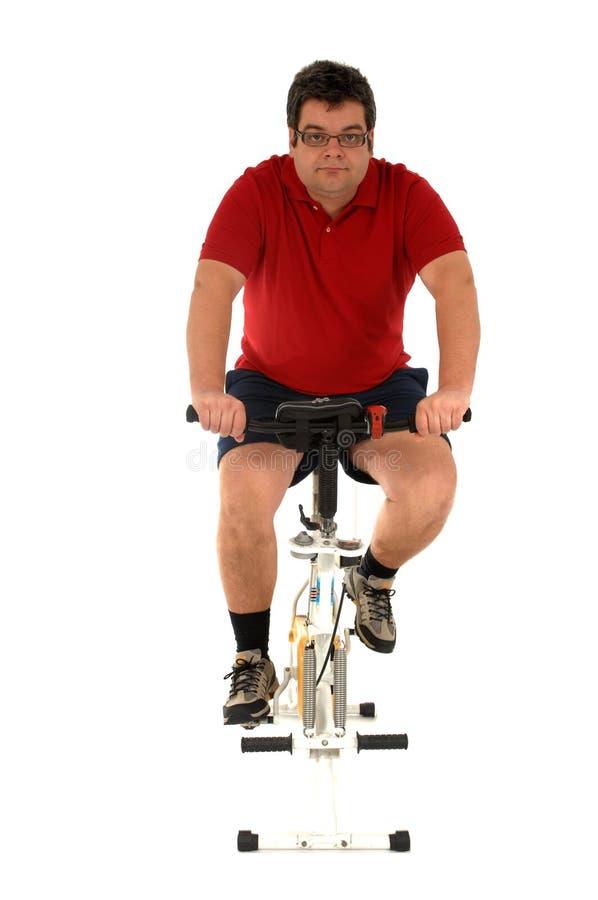 Homem que elabora com uma bicicleta de estática foto de stock