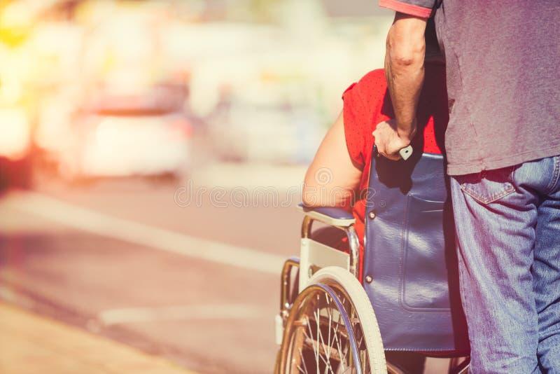 Homem que empurra a cadeira de rodas fotografia de stock royalty free