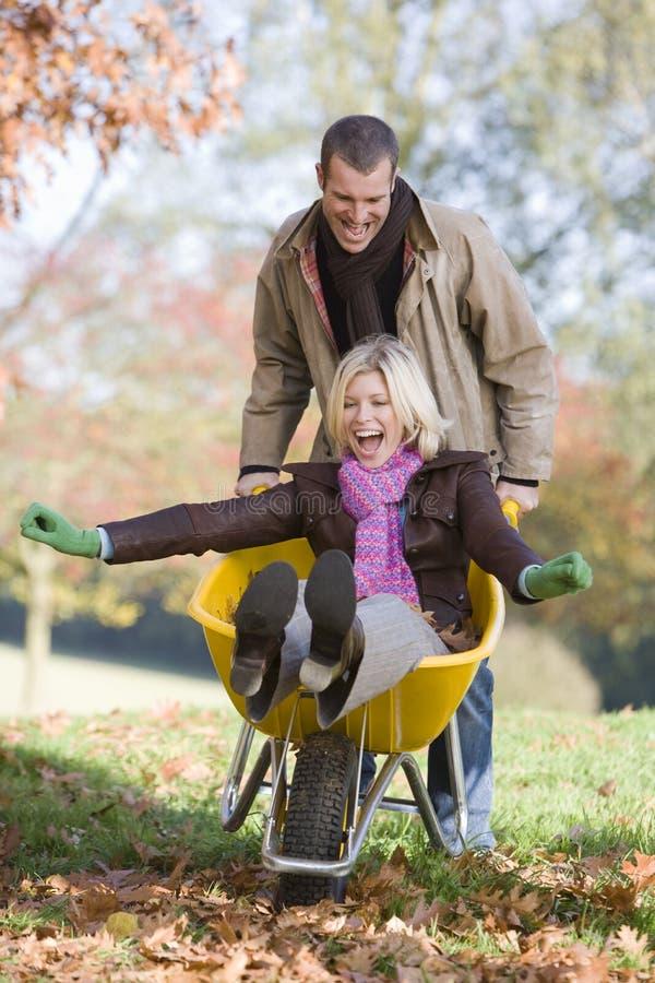 Homem que empurra a esposa no wheelbarrow fotos de stock