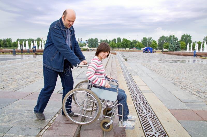 Homem que empurra a mulher na cadeira de rodas imagens de stock royalty free