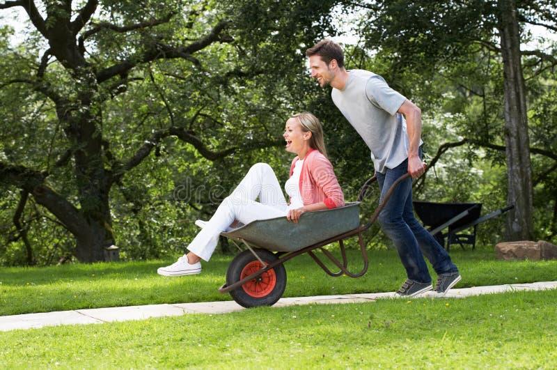 Homem que empurra a mulher no carrinho de mão foto de stock royalty free