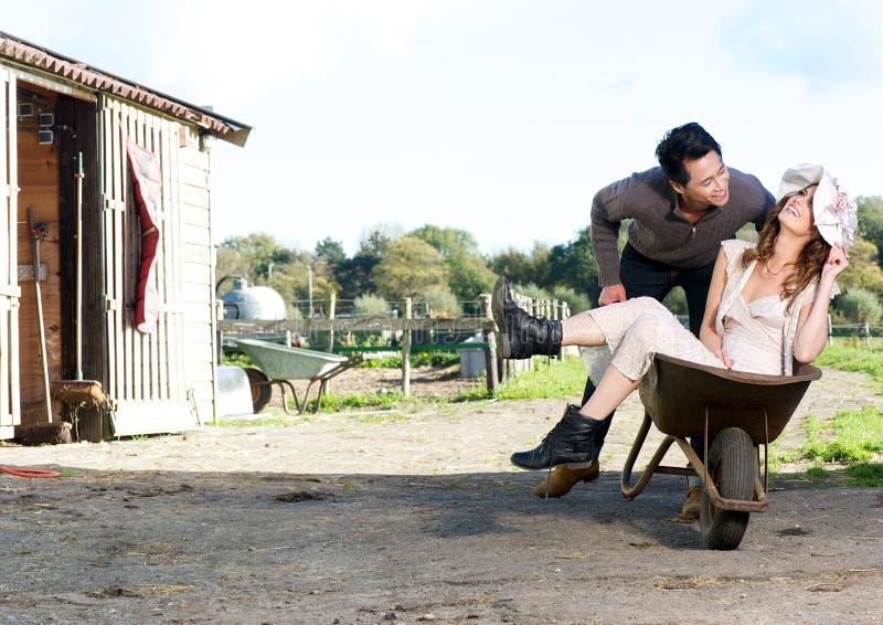 Homem que empurra a mulher no Wheelbarrow fotografia de stock royalty free