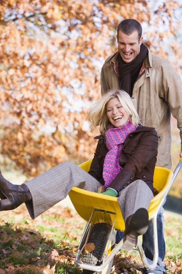 Homem que empurra a mulher no wheelbarrow foto de stock