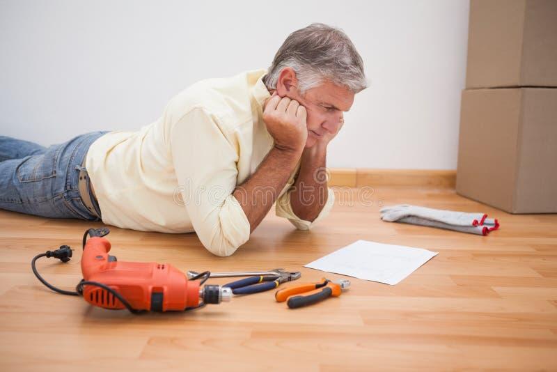 Homem que encontra-se em instruções da ferramenta da leitura do assoalho imagem de stock