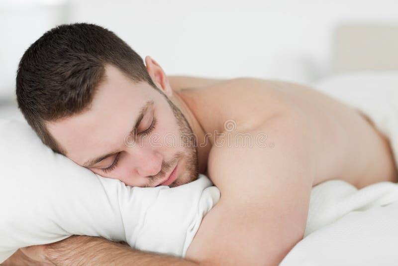 Homem que encontra-se em sua barriga ao dormir foto de stock