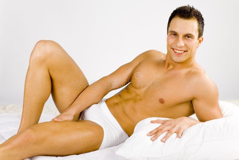 Homem que encontra-se na cama imagens de stock