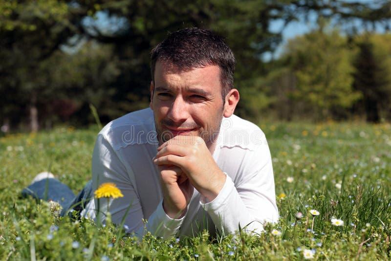 Homem que encontra-se na grama foto de stock