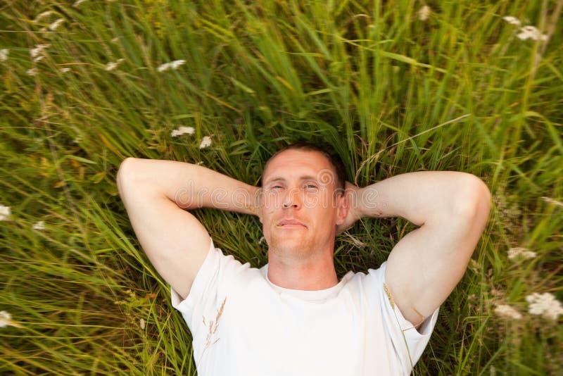 Homem que encontra-se na grama do verão foto de stock royalty free