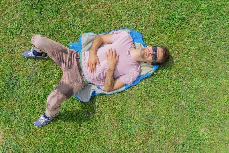 Homem que encontra-se na grama O ver?o relaxa o conceito Configura??o lisa imagem de stock