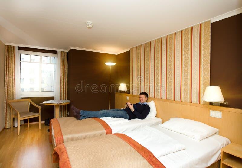 Homem que encontra-se na sala de hotel fotos de stock