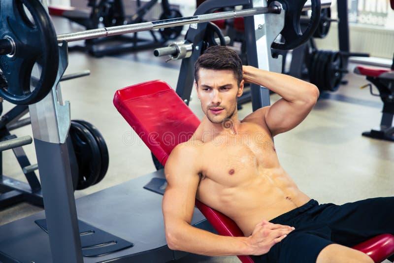 Homem que encontra-se no banco no gym imagens de stock royalty free