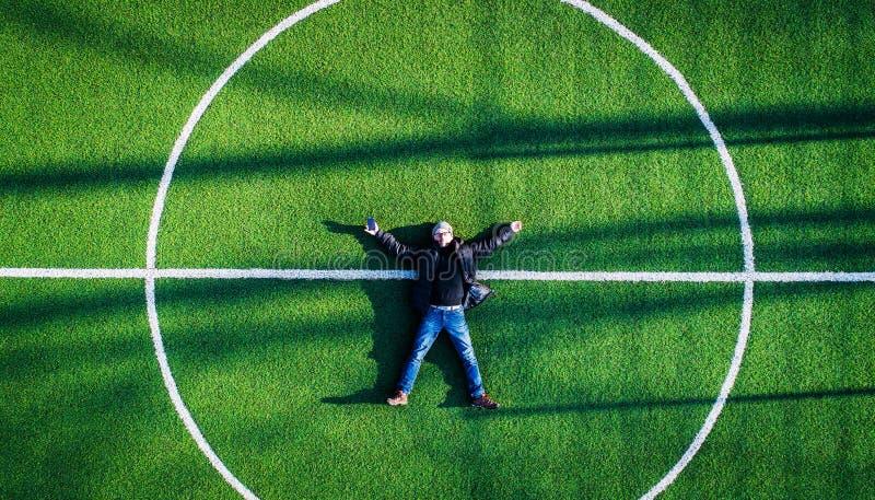 Homem que encontra-se no centro do campo de futebol, vista superior fotografia de stock royalty free