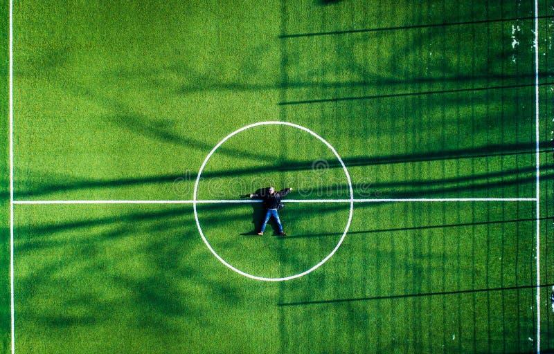 Homem que encontra-se no centro do campo de futebol, vista superior foto de stock