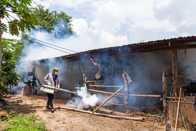 Homem que enevoa-se para impedir a propagação da febre de dengue em Tailândia fotos de stock