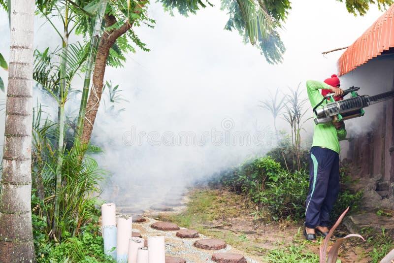 Homem que enevoa-se para impedir a propagação da febre de dengue em Tailândia imagem de stock