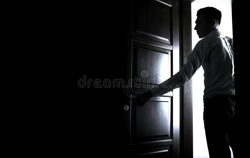 Homem que entra em um quarto escuro imagem de stock royalty free