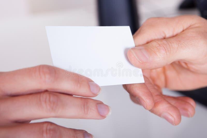 Homem que entrega a uma mulher um cartão imagem de stock royalty free