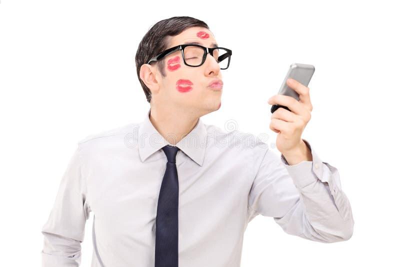 Homem que envia um beijo através de um telefone celular foto de stock