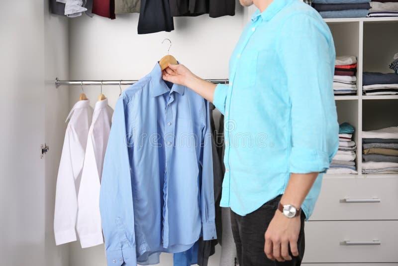 Homem que escolhe a camisa imagens de stock royalty free